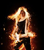 Portrait of burning young attractive blond woman playing on electric fire guitar