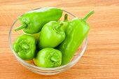 Green Peppers In Transparent Glass Bowl On Wooden Board