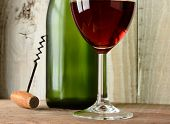 Closeup wine still life with a glass green bottle and corkscrew against a rustic wood background. Ho