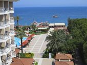 Luxurious Hotel, Palms, Swimming Pool And A Ship On Sea