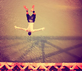 pic of trestle bridge  - a boy jumping of an old train trestle bridge into a river toned with a retro vintage instagram filter  - JPG