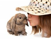 Girl in a straw hat kisses dwarf rabbit.