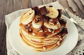 Stack of delicious pancakes with chocolate, honey, nuts and slices of banana on plate and napkin on wooden table background