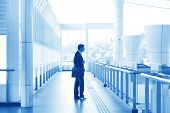 Asian Indian businessman at airport, business travel concept in blue tone.