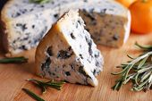Blue cheese with sprigs of rosemary and oranges on wooden board background