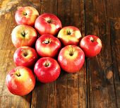 Red apples laid out in triangle on wooden background