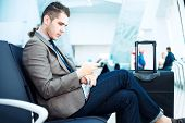 image of check  - Businessman at airport with smartphone and suitcase checking emails before boarding - JPG