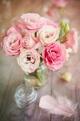 Bright romantic vertical background with roses feathers and bokeh