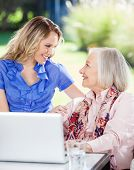 Happy granddaughter and grandmother looking at each other while using laptop on nursing home porch