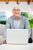 Portrait of happy senior man with laptop sitting on couch at nursing home porch