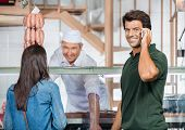 Portrait of happy mature man on call while woman buying meat in butchery