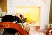 Woman and cute cat sitting on rocking chair in the front of the fireplace