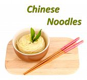 Chinese noodles in bowl on wooden board and sample text isolated on white