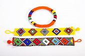stock photo of zulu  - two brightly colored zulu wristbands with beaded armband - JPG