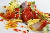Tomato salad with fish and gold leaf.