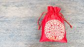 Red Silky Money Bag On Wood Desk