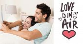 Attractive couple lying in bed with tablet pc against love is in the air