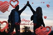 Silhouette couple holding up hands at dusk against cute valentines message