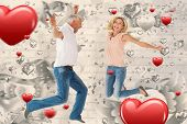 Excited couple cheering and jumping against grey valentines heart pattern