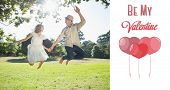 Cute couple jumping in the park together holding hands against cute valentines message