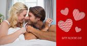 Cute couple relaxing on bed smiling at each other against cute valentines message