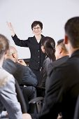 foto of motivation talk  - Hispanic woman standing in front speaking to group of business people - JPG