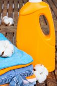 orange bottle of detergent and cotton clothes