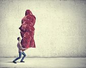 pic of heavy bag  - Young man in casual carrying heavy red bag - JPG