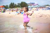 Happy young girl running into the waves at the beach