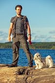 Young man tourist with shih-tzu dog walking on lake shore.