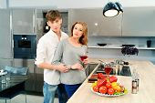 Happy young couple in love cooking a dinner on a kitchen and drink red wine. Healthy food. Happy family.