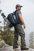 Young man tourist with backpack and tripod standing on mountain top at rainy weather.