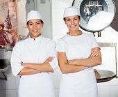 Portrait of confident female butchers smiling in butchery