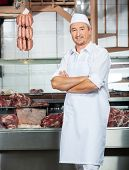 Portrait of mature male butcher standing arms crossed at display cabinet in butchery
