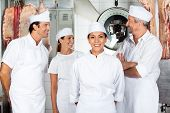 Portrait of confident female butcher with colleagues in butchery