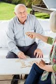 Happy senior man playing dominoes with woman at nursing home porch