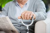 Midsection of senior man with newspaper and metal cane sitting on couch at nursing home porch