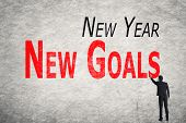 Asian business man write words on wall, New Year New Goals