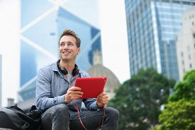 stock photo of late 20s  - Urban man using tablet computer sitting in Hong Kong outside using app on 4g wireless device wearing headphones - JPG