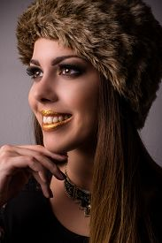 picture of vivacious  - Vivacious smiling winter fashion model in a fur hat and knitwear looking to the side with her hand to her chin close up face portrait - JPG