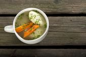 stock photo of matzah  - Soup with dumplings on a rustic wooden table - JPG