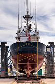 stock photo of shipyard  - Stern view of a fishing boat in a shipyard for maintenance - JPG