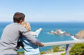 image of binoculars  - father and his son using binoculars together and enjoying the view of california coast - JPG