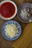 image of grating  - Spaghetti ingredients, close up; tomatoe saucen grated cheese, salt and nutmeg