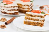pic of sponge-cake  - Delicious slice of carrot sponge cake with icing cream and little orange carrots on white background - JPG