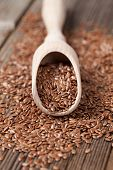 image of flax plant  - Heap of vegetarian nutrition flax seeds with omega fat in spoon on vintage wooden background - JPG
