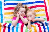 picture of little young child children girl toddler  - Two kids sleeping in bed under colorful blanket - JPG