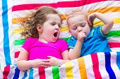 pic of little young child children girl toddler  - Two kids sleeping in bed under colorful blanket - JPG