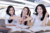 image of joining hands  - Portrait of beautiful teenage girls joining their hands together in the class - JPG