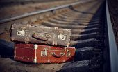 image of old suitcase  - Two old suitcases are left to lie on railway rails - JPG